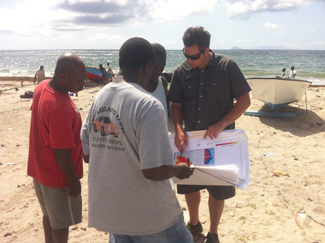 Charles Steinback of Ecotrust verifies maps of fishing areas with local fishers. Photo © Shawn W. Margles/TNC